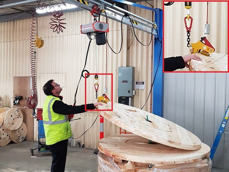 Jib crane with custom plate grab on hoist for round timber reel ends